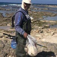Yussuf avec les poissons qu'il a ramassés sur la plage d'Achziv dans le nord d'Israël, le 25 février 2021. (Crédit :  Sue Surkes/Times of Israel)
