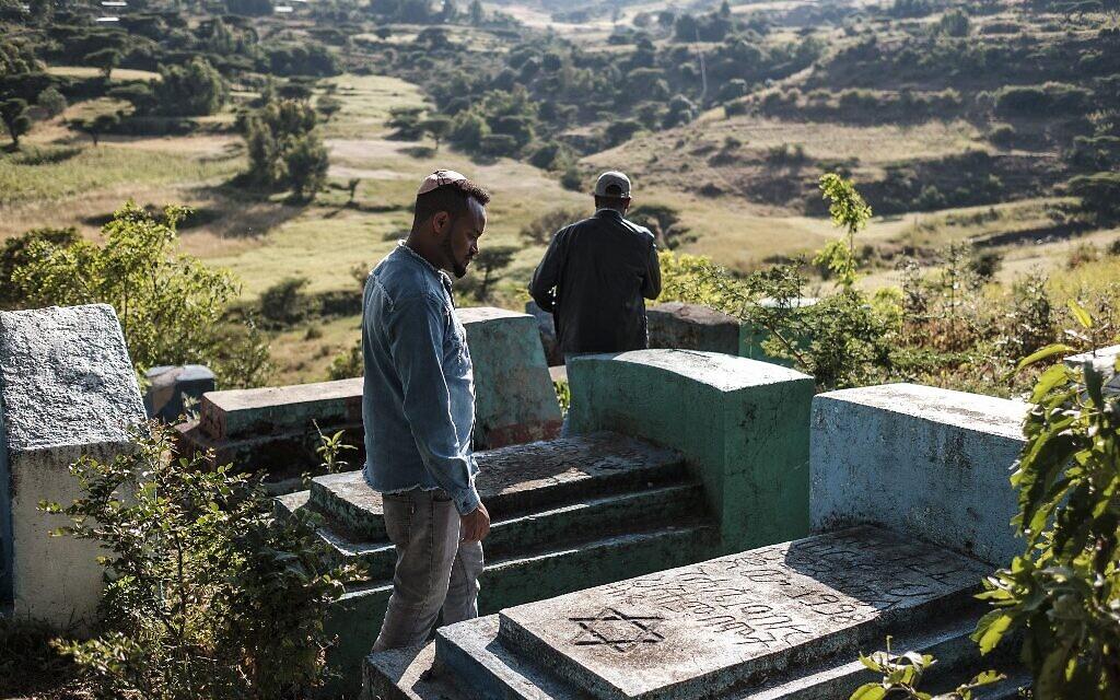Sitotaw Alene (à droite) et Adamu Mengistu, dirigeants de la communauté juive éthiopienne, visitent le cimetière de la communauté à la périphérie de la ville de Gondar, en Ethiopie, le 26 octobre 2020. (Crédit : EDUARDO SOTERAS / AFP)