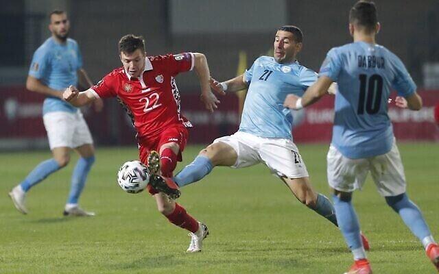 Le milieu de terrain moldave Vadim Rata et le défenseur israélien Eitan Tibi luttent pour le ballon lors du match de football de qualification pour la Coupe du Monde de la FIFA, Qatar 2022, Moldavie contre Israël, au stade Zimbru de Chisinau, le 31 mars 2021. (Crédit : Bogdan TUDOR / AFP)
