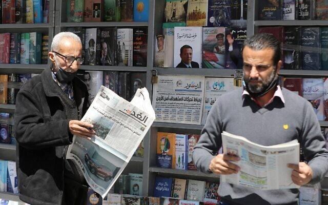 """Des hommes jordaniens lisent des journaux locaux avec des titres en première page sur les derniers événements dans leur pays, devant un kiosque dans la capitale Amman, le 4 avril 2021. Les médias officiels jordaniens ont prévenu aujourd'hui que la sécurité et la stabilité constituaient une """"ligne rouge"""", au lendemain de l'arrestation de plusieurs personnalités et de la mise en résidence surveillée d'un demi-frère du roi Abdallah II. (Khalil MAZRAAWI / AFP)"""