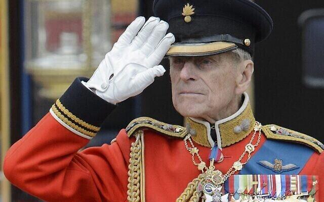 Le prince Philip de Grande-Bretagne, le duc d'Édimbourg, salue alors qu'il observe les troupes devant le palais de Buckingham après le défilé de l'anniversaire de la reine à Londres, le 16 juin 2012. (Crédit : LEON NEAL / AFP)