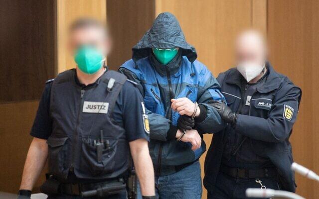 """Un accusé est escorté par des officiers de justice pour l'ouverture d'un procès contre douze hommes accusés d'avoir créé et soutenu une organisation terroriste, le """"Groupe S"""" (Gruppe S.), le 13 avril 2021 au tribunal de Stuttgart - Stammheim, dans le sud de l'Allemagne. Le groupe, qui porte le nom de son chef Werner S., est soupçonné d'avoir planifié des attaques contre des mosquées et des hommes politiques. (POOL / AFP)"""