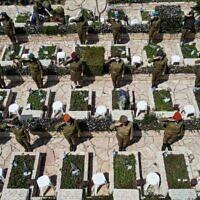 Des soldates israéliennes effectuant des saluts près de tombes au cimetière militaire de Kiryat Shaul, à Tel Aviv, à l'occasion de Yom HaZikaron, le 14 avril 2021. (Crédit : JACK GUEZ / AFP)