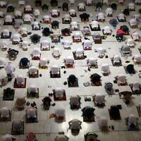 Des fidèles musulmans effectuent la prière de Tarawih pendant le mois de jeûne du Ramadan autour de la Kaaba dans le complexe de la Grande Mosquée de la ville sainte de La Mecque, le 13 avril 2021. (Crédit : AFP)