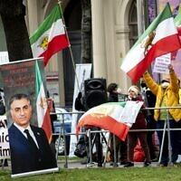 Des membres du Conseil national de la résistance iranienne, un groupe d'opposition iranien, manifestent devant le Grand Hôtel Wien, où se déroulent les négociations nucléaires à huis clos avec l'Iran, à Vienne, le 15 avril 2021. Les diplomates de l'UE, de la Chine, de la Russie et de l'Iran y tiennent leurs discussions. (Crédit : JOE KLAMAR / AFP)