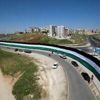 Une photo montre des ouvriers de la municipalité d'Amman installant un drapeau jordanien de 2132 mètres de long visant à battre le record du monde Guinness du plus long drapeau du monde, le 15 avril 2021 dans la capitale jordanienne. (Crédit : Khalil MAZRAAWI / AFP)