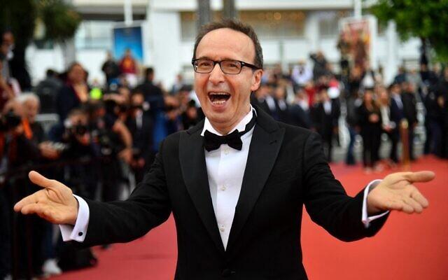 """Sur cette photo d'archive prise le 13 mai 2018, l'acteur et réalisateur italien Roberto Benigni réagit en arrivant à la projection du film """"Heureux comme Lazzaro (Lazzaro Felice)"""" lors de la 71e édition du Festival de Cannes à Cannes, dans le sud de la France. L'acteur et réalisateur italien Roberto Benigni, qui a remporté un Oscar pour """"La vie est belle"""", sera honoré d'un prix pour sa carrière lors du Festival du film de Venise de cette année, ont annoncé les organisateurs le 15 avril 2021. (ALBERTO PIZZOLI / AFP)"""