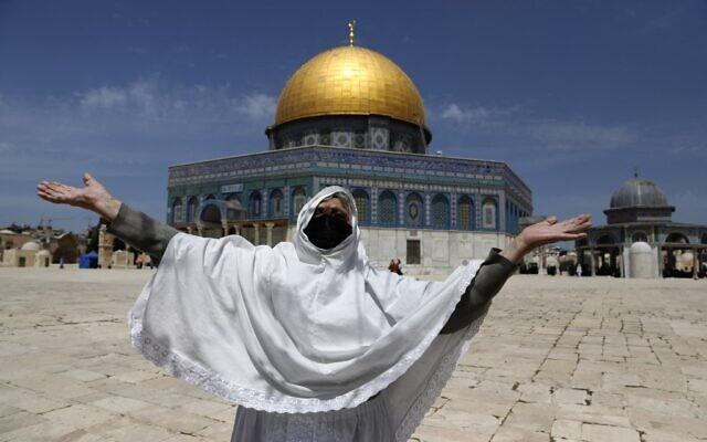 Une femme palestinienne lève les bras pour la première lors de la première prière du vendredi du Ramadan aux abords du Dôme des roches, sur le mont du Temple de Jérusalem, le 26 avril 2021. (Crédit : Ahmad GHARABLI / AFP)