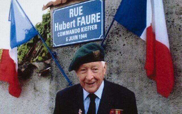 Hubert Faure, ancien membre des commandos Kieffer, groupe de 177 soldats français ayant participé à l'invasion de la Normandie connue sous le nom d'Opération Overlord pendant la Seconde Guerre mondiale, devant une plaque de rue portant son nom à Neuvic-sur-Isle, en 2008. (Crédit : AFP)