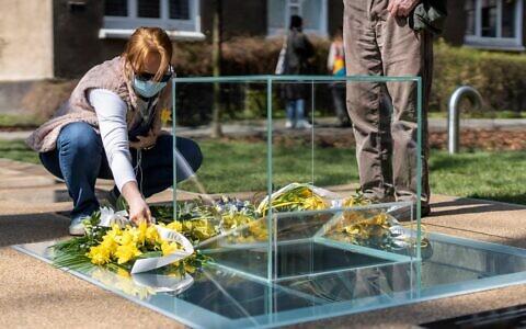 Ds Polonais déposent une gerbe et des fleurs devant un monument dédié aux archives souterraines du ghetto juif de Varsovie, lors de son inauguration sur le site où les archives Ringelblum ont été cachées pendant l'occupation nazie pendant la Seconde Guerre mondiale, à Varsovie, le 19 avril, 2021 (Crédit : Wojtek RADWANSKI / AFP)