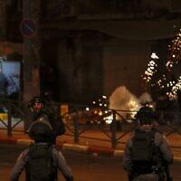 Des Palestiniens fuient les grenades incapacitantes des forces de sécurité israéliennes dans un cadre d'affrontements entre des Juifs d'extrême-droite et des contre-manifestants arabes dans la Vieille Ville de Jérusalem, le 22 avril 2021. (Crédit :  AHMAD GHARABLI / AFP)