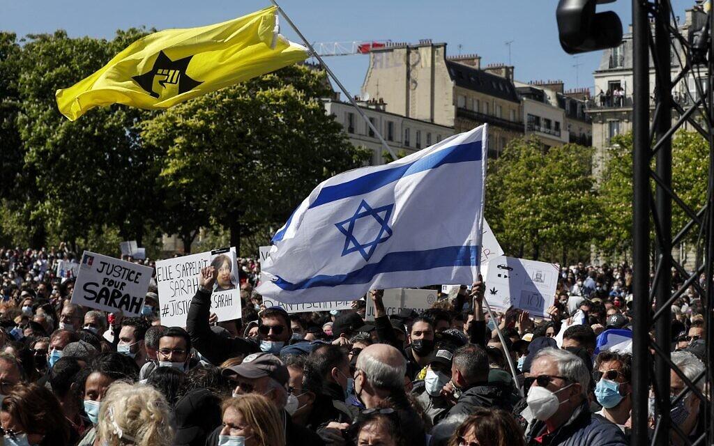 Un homme brandit un drapeau d'Israël à côté d'un drapeau de la Ligue de défense juive au rassemblement pour demander justice pour Sarah Halimi, sur la place du Trocadéro, devant la tour Eiffel, à Paris, le 25 avril 2021. (Crédit : GEOFFROY VAN DER HASSELT / AFP)