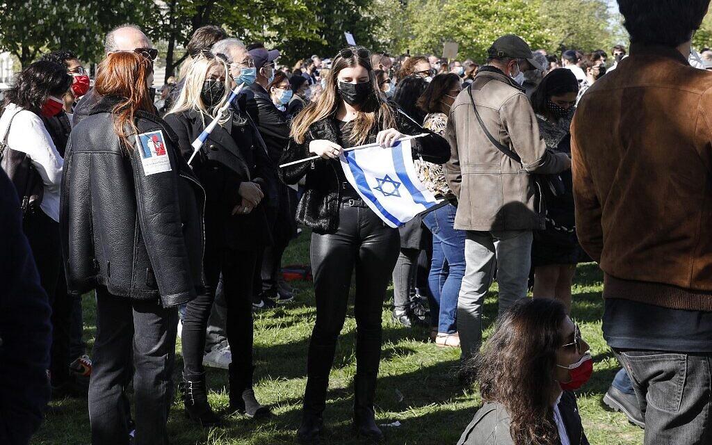 Une femme brandit un drapeau d'Israël lors du rassemblement pour demander justice pour Sarah Halimi, sur la place du Trocadéro, devant la tour Eiffel, à Paris, le 25 avril 2021. (Crédit : GEOFFROY VAN DER HASSELT / AFP)