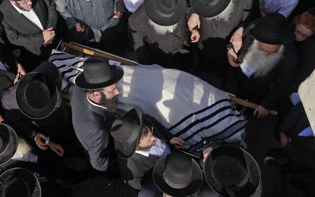 Des hommes juifs ultra-orthodoxes participent à une cérémonie funéraire à Jérusalem pour la victime d'un mouvement de foule meurtrier la nuit précédente lors du rassemblement de Lag B'Omer dans le nord d'Israël, le 30 avril 2021. (Crédit : Menahem KAHANA / AFP)