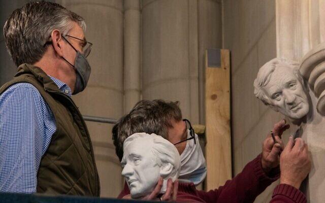 Sur cette photo non datée, le sculpteur Chas Fagan, (à gauche), tient un modèle en argile d'un buste d'Elie Wiesel et regarde le tailleur de pierre Sean Callahan, (à droite), utiliser des techniques médiévales pour sculpter le buste dans les murs de la cathédrale nationale de Washington DC. (Cathédrale nationale/ via JTA)