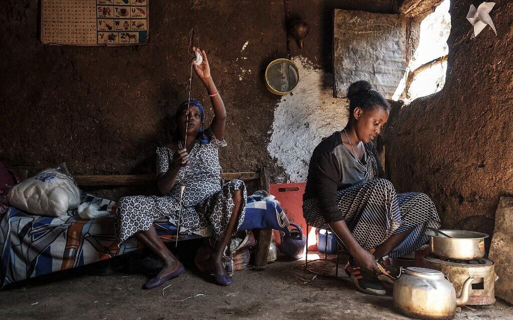 Une femme membre de la communauté juive éthiopienne tricote tandis qu'une autre cuisine, dans la ville de Gondar, en Ethiopie, le 27 octobre 2020. (Crédit : EDUARDO SOTERAS / AFP)