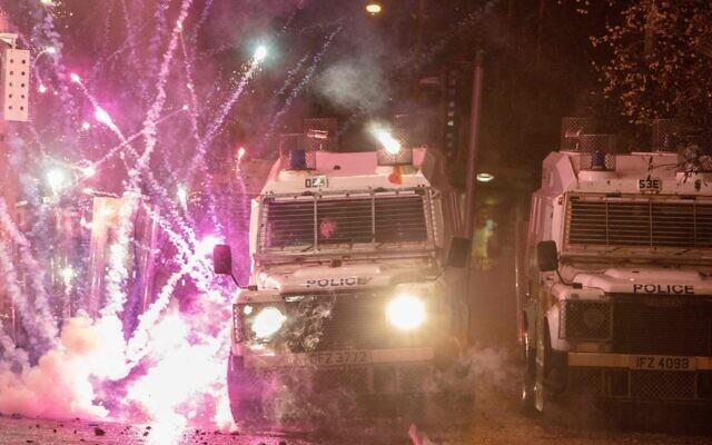 Des feux d'artifice lancés par des émeutiers explosent sur des véhicules de police à Belfast, le 8 avril 2021. (Paul Faith/AFP/Getty Images via JTA)