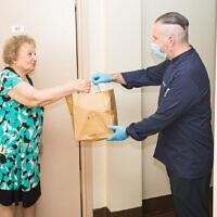 David Teyf, PDG et chef exécutif de Madison and Park, livre des repas à des survivants de la Shoah résidant dans un immeuble du MetCouncil dans le Lower East Side à New York, le 21 août 2020. (Crédit : Benjamin Kanter/JTA)