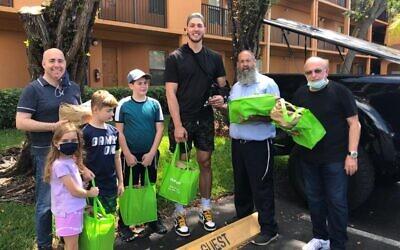 Meyers Leonard, au centre, distribue des repas de Pessah à des survivants de la Shoah et des seniors juifs dans la région de Miami avec l'aide du rabbin Pinny Andrusier, à sa gauche. (Crédit : Chabad of Southwest Broward via JTA)