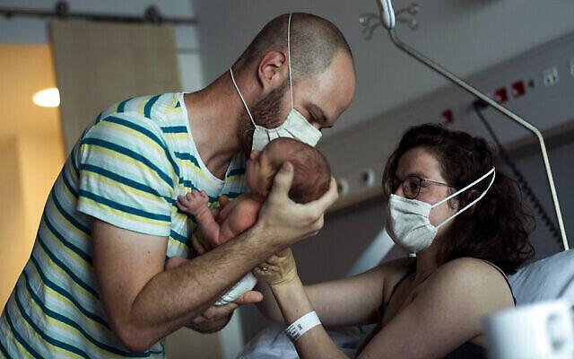 Un père portant un masque facial pour se protéger contre le coronavirus, amène sa fille nouvelle-née à sa mère pour qu'elle l'allaite, à Liège, en Belgique, le vendredi 26 juin 2020. (AP Photo / Francisco Seco)