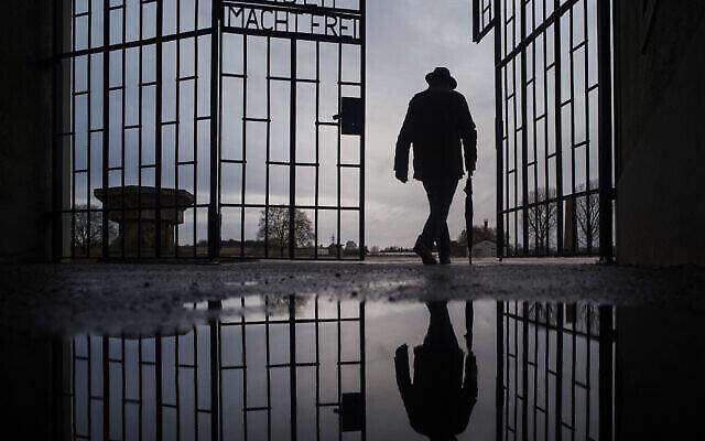"""Un homme franchit la porte du camp de la mort nazi de Sachsenhausen avec la phrase """"Arbeit macht frei"""" (le travail rend libre) à Oranienburg, en Allemagne, lors de la Journée internationale de commémoration de la Shoah, le 27 janvier 2019. (Markus Schreiber/AP)"""