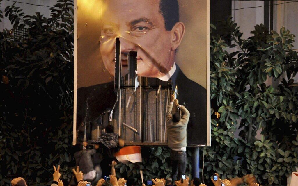 Des manifestants dégradent une affiche du président égyptien Hosni Moubarak à Alexandrie, en Égypte, le 25 janvier 2011. (Crédit : AP)