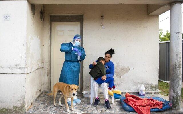 Un employé se prépare à effectuer un test de dépistage au coronavirus sur un enfant dans une banlieue de Montevideo, en  Uruguay, le 18 mars 2021. (Crédit : AP Photo/Matilde Campodonico)
