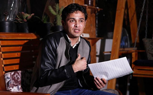 Rami Aman, un militant pacifiste palestinien de Gaza, montre les notes dans lesquelles il a consigné son calvaire lors d'une interview sur le toit de la maison familiale à Gaza, le 10 février 2021. (Crédit : Adel Hana / AP)