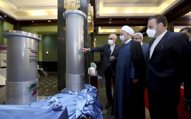 Le président Hassan Rouhani, deuxième à droite, écoute le chef de l'Organisation de l'énergie atomique iranienne, Ali Akbar Salehi lors d'une visite d'une exposition sur les récentes avancées nucléaires à Téhéran, en Iran, le 10 avril 2021. (Crédit : Bureau de la présidence iranienne via AP)