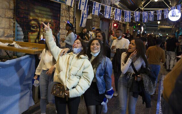 Des femmes israéliennes fêtent Yom HaAtsmaout au marché Mahane Yehuda à Jérusalem, après plus d'un an de restrictions liées au coronavirus, le 14 avril 2021. (Crédit : AP Photo/Maya Alleruzzo)