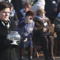 La Premier ministre polonaise de l'époque, Beata Szydlo, allume une bougie au Monument international aux victimes du fascisme, après une cérémonie marquant le 72e anniversaire de la libération du camp d'extermination nazi allemand d'Auschwitz-Birkenau, à Oswiecim, en Pologne, le 27 janvier 2017. (Crédit : AP Photo / Czarek Sokolowski)