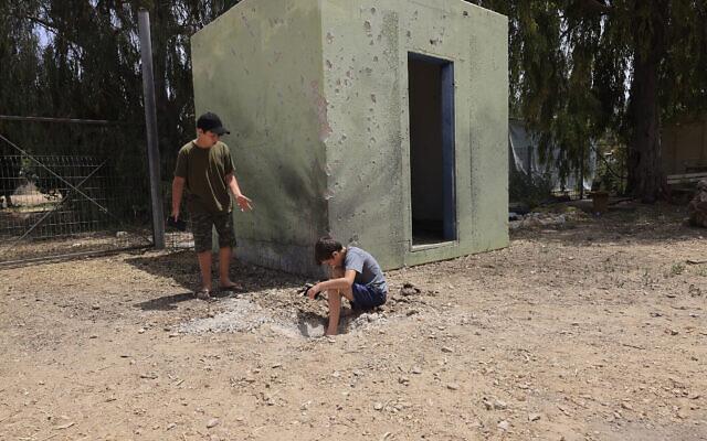 Des garçons israéliens examinent le site où une roquette tirée depuis la bande de Gaza a atterri en Israël, le 24 avril 2021. (AP Photo/Tsafrir Abayov)
