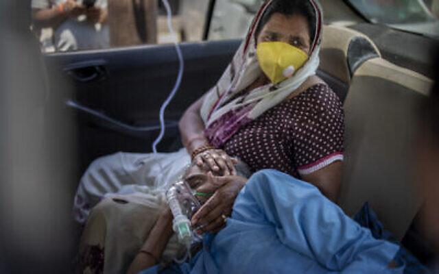 Une patiente respire à l'aide d'oxygène fourni par un Gurdwara, lieu de culte sikh, à l'intérieur d'une voiture à New Delhi, en Inde, le 24 avril 2021. (Altaf Qadri/AP)