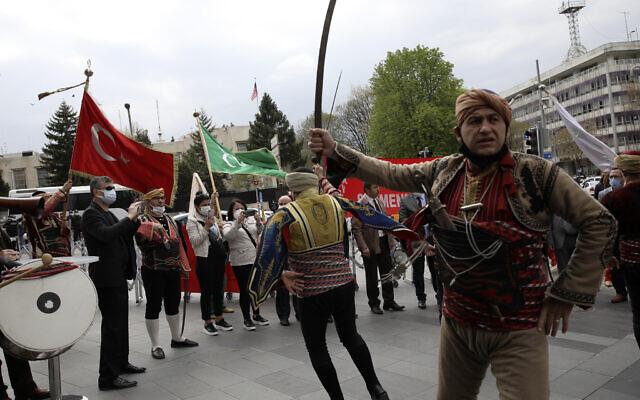Des soldats américains montent la garde sur le toit de l'ambassade des États-Unis, à l'arrière-plan, alors que des membres du club d'Ankara appelé Seymen dansent en habits traditionnels lors d'une manifestation contre une déclaration du président américain Joe Biden, à Ankara, en Turquie, lundi 26 avril 2021. (AP Photo/Burhan Ozbilici)