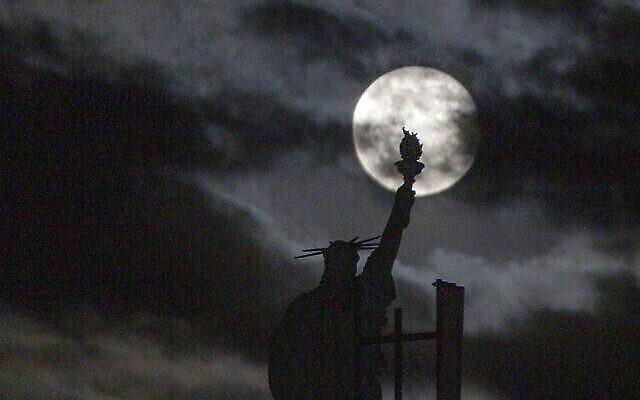 La super lune rose au dessus d'une réplique de la statue de la Liberté au kosovo, le 27 avril 2021. (Crédit : AP Photo/Visar Kryeziu)