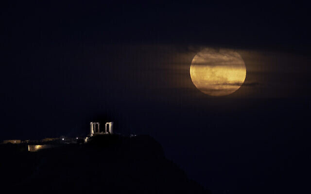 La super lune rose au dessus du temple de Poséidon au cap Sounion, en Grèce, le 17 avril 2021. (Crédit : AP Photo/Petros Giannakouris)