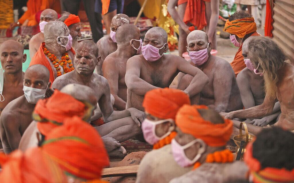 Des Naga Sadhu, hommes saints hindous nus, attendent le départ d'une procession vers le fleuve Ganges pour le Shahi Snan (bain royal) pendant la Kumbh Mela, à Haridwar dans l'état indien d'Uttarakhand, lundi 12 avril 2021. Alors que les États indiens décrètent une forme de confinement pour lutter contre la hausse des cas de COVID-19 dans le cadre d'une deuxième vague nationale, des milliers de pèlerins se rassemblent sur les rives du Gange pour la fête hindoue. Les fidèles croient qu'un plongeon dans les eaux du Gange les absoudra de leurs péchés et les délivrera du cycle de la naissance et de la mort. (AP Photo/Karma Sonam)