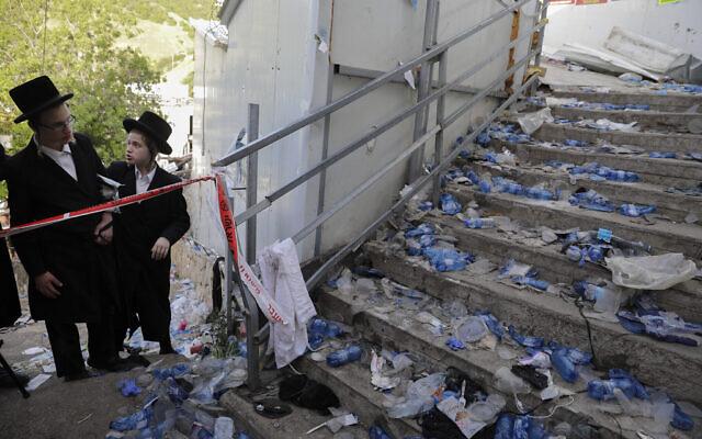 Des Juifs ultra-orthodoxes contemplent le site d'une bousculade mortelle lors des festivités de Lag BaOmer au Mont Meron, dans le nord d'Israël, le 30 avril 2021. (Crédit : AP Photo/Sebastian Scheiner)