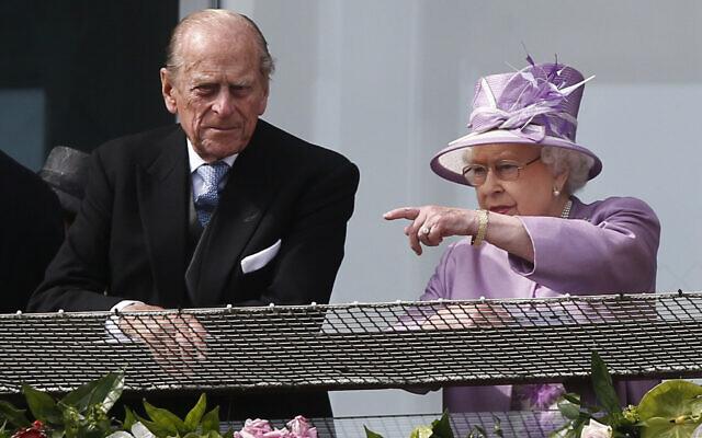 La reine Elizabeth II de Grande-Bretagne fait remarquer quelque chose au prince Philip alors qu'ils regardent le Derby d'Epsom depuis le balcon de l'hippodrome d'Epsom, en Angleterre, le 7 juin 2014. (AP Photo/Sang Tan)