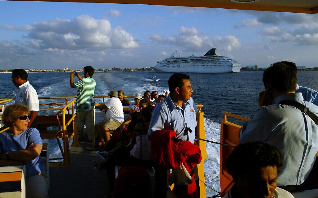 Illustration : Des touristes contemplent le paysage alors qu'ils retournent à Playa del Carmen après avoir visité l'île de Cozumel, au Mexique, le 14 décembre 2005. (AP Photo/Guillermo Arias)