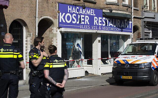 Illustration : Un drapeau israélien dépasse de la fenêtre du restaurant casher HaCarmel à Amsterdam, aux Pays-Bas, le 8 mai 2020, après qu'un homme a brisé la fenêtre. (Photo AP / Peter Dejong)