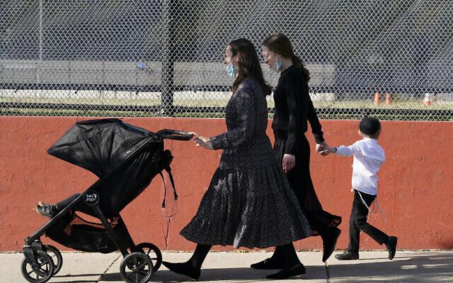 Deux jeunes femmes marchent avec des enfants pendant la fête juive de Souccot dans le quartier de Borough Park, dans l'arrondissement de Brooklyn, à New York, le 4 octobre 2020. (AP/Kathy Willens)