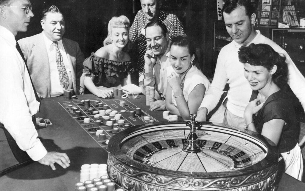 Des personnes se trouvent à l'une des tables de jeu du casino Flamingo à Las Vegas, Nevada, le 24 mai 1955. (Photo AP)