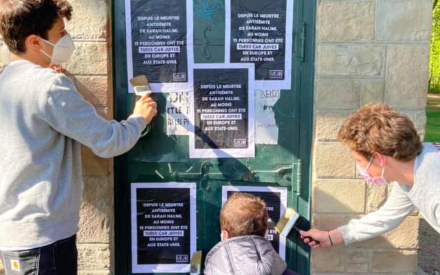Des jeunes de l'UEJB collent des affiches contre l'antisémitisme, à Bruxelles, le 25 avril 2021. (Crédit : UEJB)