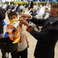 Le président de l'Agence juive Isaac Herzog et Gila Gutman Azulay, une parente des personnes décédées sur le navire Egoz, allument une torche pour commémorer les victimes du naufrage, le 14 avril 2021. (The Jewish Agency for Israel)