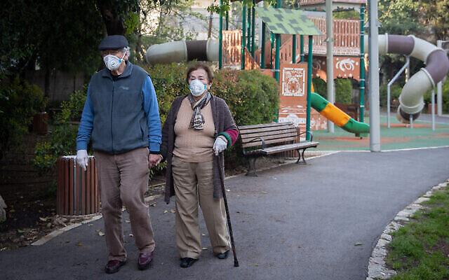 Un couple de personnes âgées se promène dans un parc public du quartier Rehavia de Jérusalem, le 13 avril 2020. (Crédit : Yonatan Sindel / Flash90)