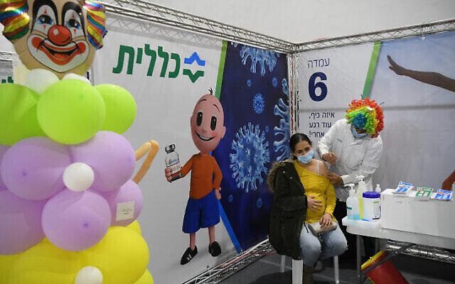 Une femme enceinte reçoit un vaccin COVID-19 dans un centre Clalit à Or Yehuda, le 25 février 2021. L'infirmière portait une perruque colorée en l'honneur de la fête de Pourim. (Flash90)
