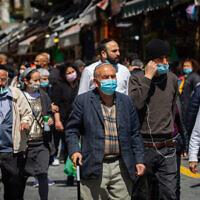 Des gens portent des masques au marché Mahane Yehuda à Jérusalem, le 17 mars 2021. (Crédit : Olivier Fitoussi / Flash90)