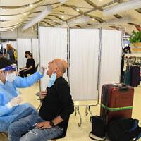 Des employés du secteur médical dépistent les passagers au coronavirus à l'aéroport international Ben-Gurion, près de Tel Aviv, le 8 mars 2021. (Crédit : Flash90)