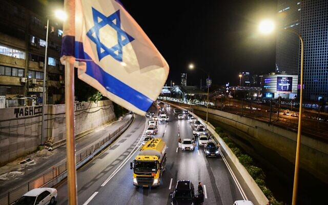 Des conducteurs israéliens restent immobiles sur l'autoroute Ayalon à Tel Aviv alors qu'une sirène d'une minute retentit à travers tout Israël, marquant Yom HaZikaron qui commémore les soldats israéliens tombés au combat et les victimes du terrorisme, le 13 avril 2021. (Crédit : Avshalom Sassoni / Flash90)